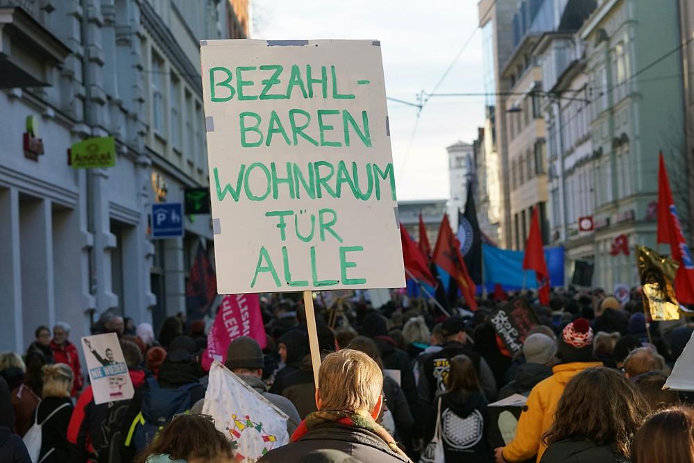 """Straßendemo und ein Mann hält ein Schild mit der Aufschrift """"Bezahlbaren Wohnraum für alle"""""""