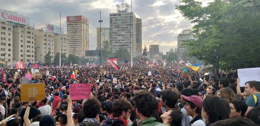 Überfüllter Platz mit Tausenden Demonstrierenden und Plakaten sowie Fahnen