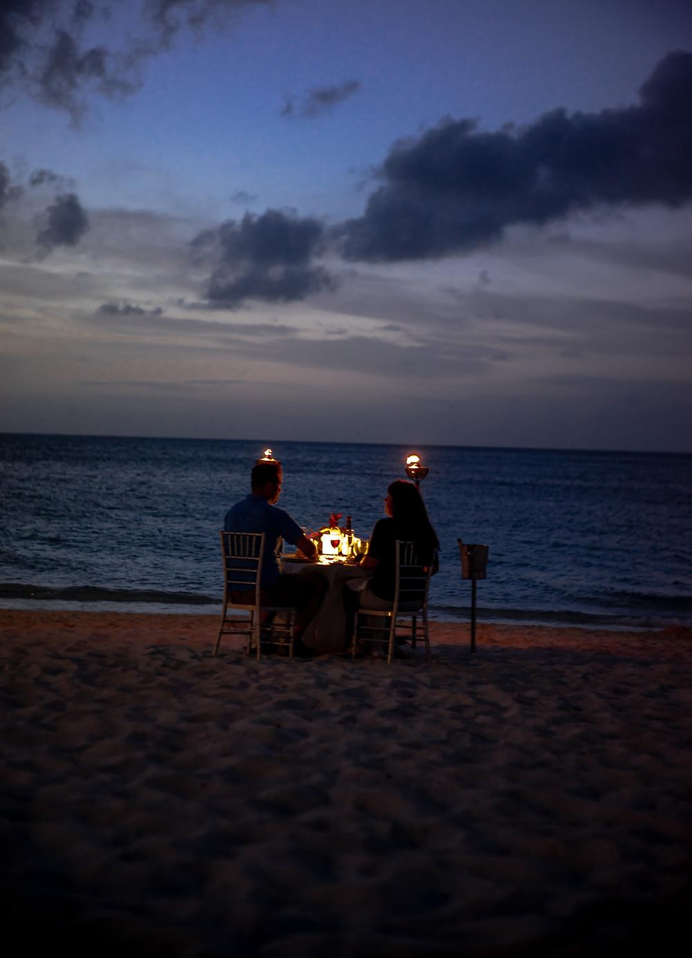 Candle Light Dinner eines Paares am Strand bei Kerzenschein