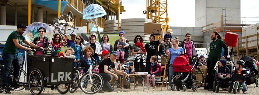 Unterschiedliche Menschen unterschiedlicher Generationen stehen in der Gruppe zusammen auf einer Baustelle und halten Fahrräder, Schirme und Kinder in die Höhe.