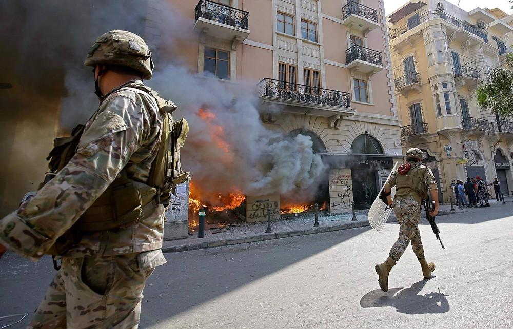 Soldaten vor einer brennenden Bankfiliale