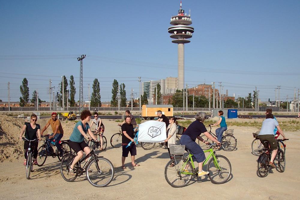 Auf einem ausgehobenen Fundament fährt die Gruppe von Bikes and rails mit ihren Fahrrädern um zwei Männer im Kreis, die das Banner von B&R halten