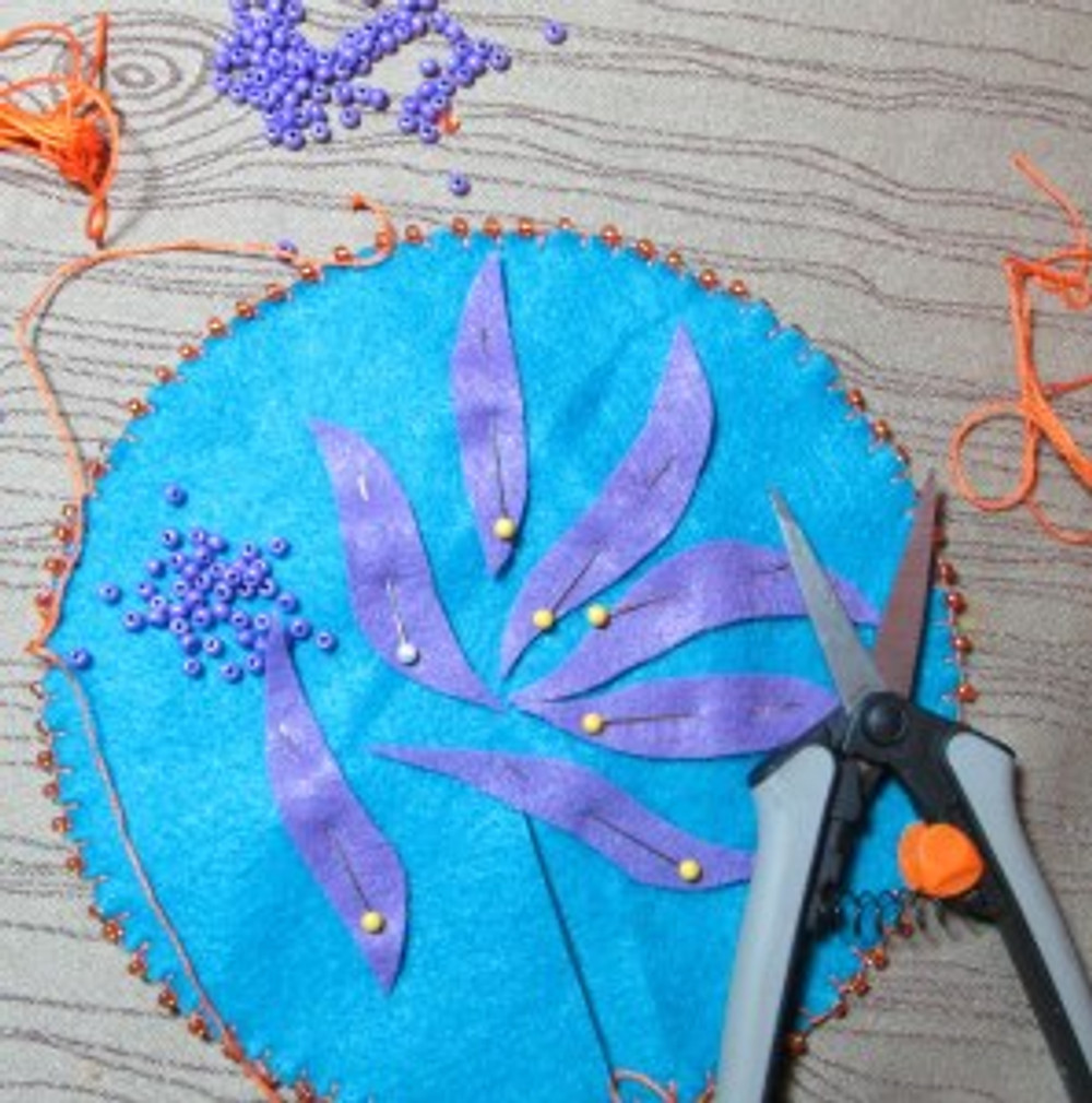 For this bundle I did a blanket stitch around the edges to keep the felt from fraying and added orange beads.  I then cut out felt pieces that spoke to me of recovery and transformation -- all free hand -- let your creative power go!