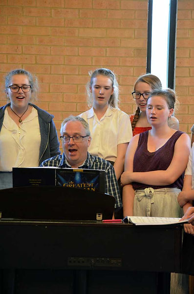 Craig MacLeish with MK Youth Choir singing popular songs around the piano