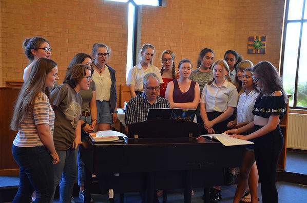 MK Youth Chorale (Seniors) singing around Craig at the piano