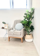 Landing space styling with an armchair and decorative accessories including faux plants.