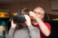 Man helps boy with VR headset