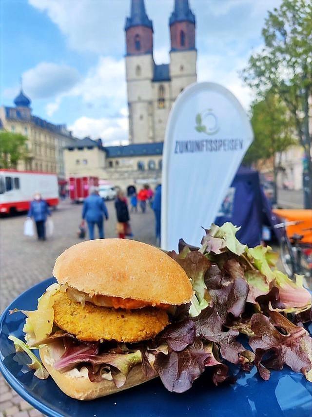 Zu sehen ist ein Burger mit Salat. Im Hintergrund sieht man den Aufsteller von Zukunftsspeisen und einen Marktplatz mit einer Kirche im Hintergrund.