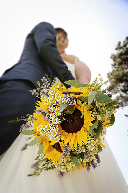 Bride and groom holding a bouquet of sunflowers on their wedding day in North Wales