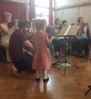 A youngster tries conducting the orchestra
