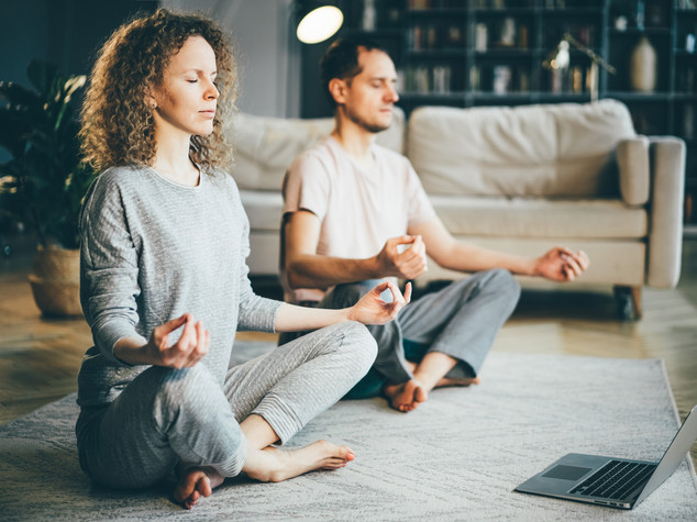 Calm couple in pajamas meditating, liste