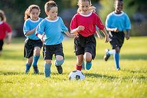 Crianças que jogam o futebol