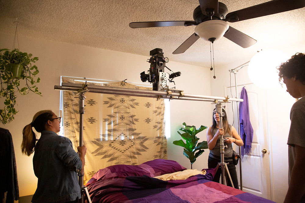 Two females are creating a bird eye view above a bed by setting a camera above the bed with some stands