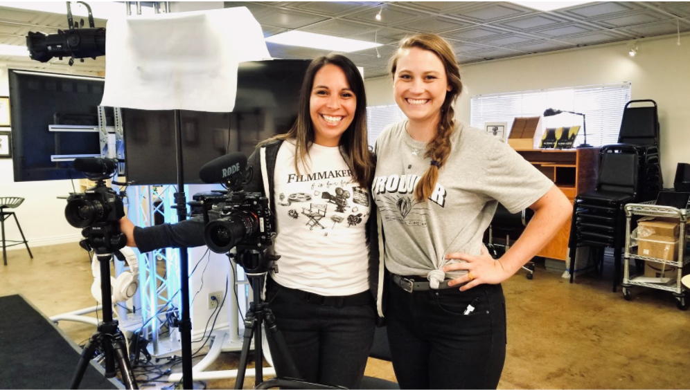 A photo of Natalie and Meredith smiling near two cameras and a light set up.