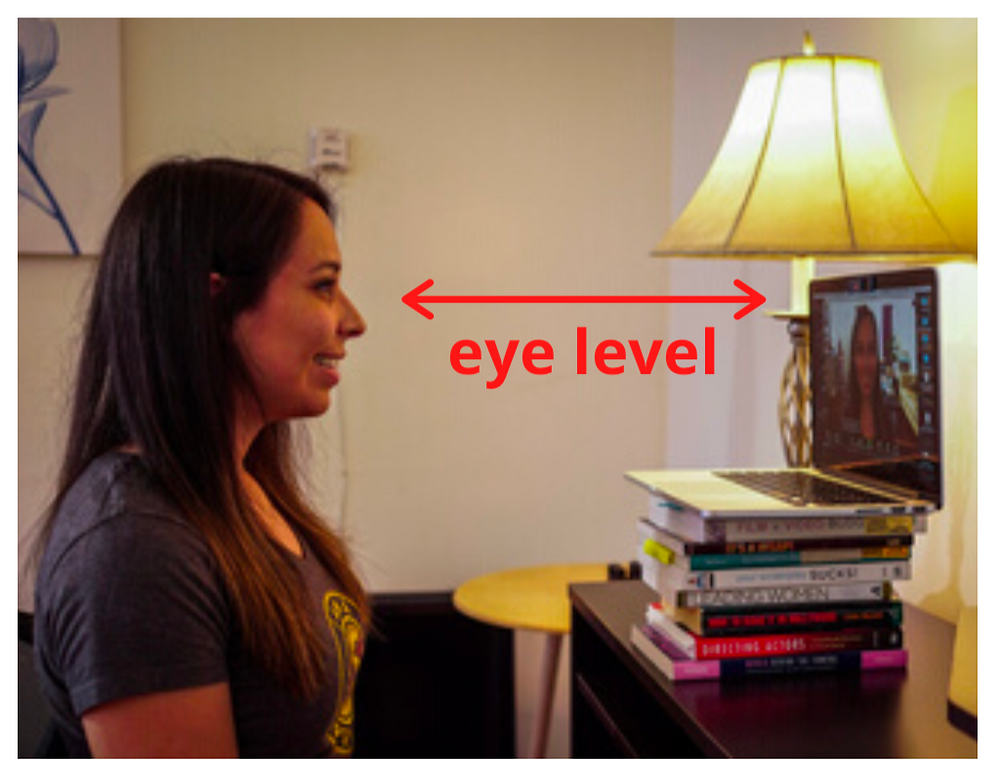 A laptop is sitting on stacked up books so that the camera of the laptop is eye level with Natalie, sitting at the desk.