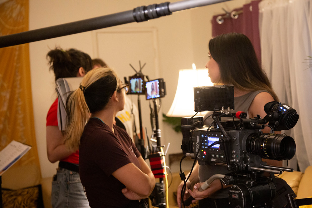 A picture taken of a female crew standing and talking about how the shot of a clip came out and they are surrounded with cameras.with