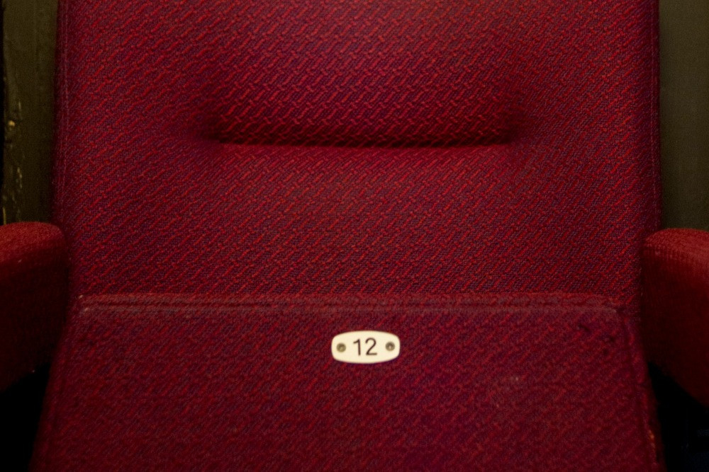 A red cinema seat with the number 12