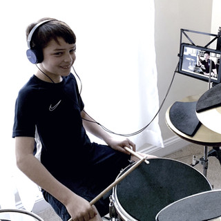 Child having online drumming tuition from drum tutor