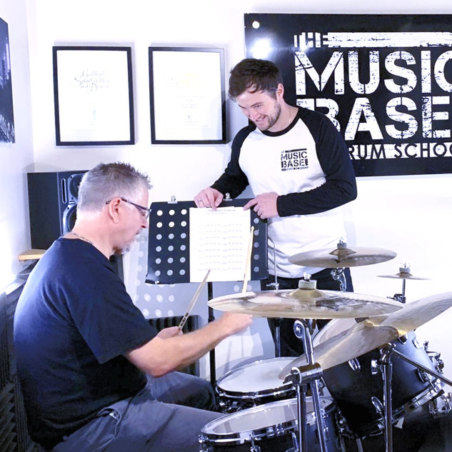 Adult drummer having private drumming tuition in music studio