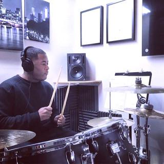 Beginner drummer having tuition on drum kit
