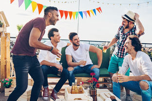 Group of young men laughing at an outside BBQ
