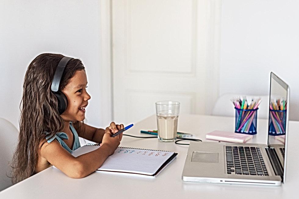 little-hispanic-girl-studying-in-front-o
