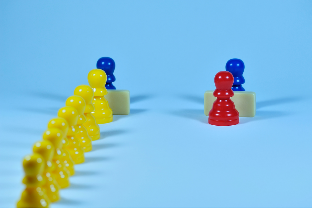 Two lines of pegs in the shape of people. One line has a single red peg waiting, the second line has multiple yellow pegs waiting.