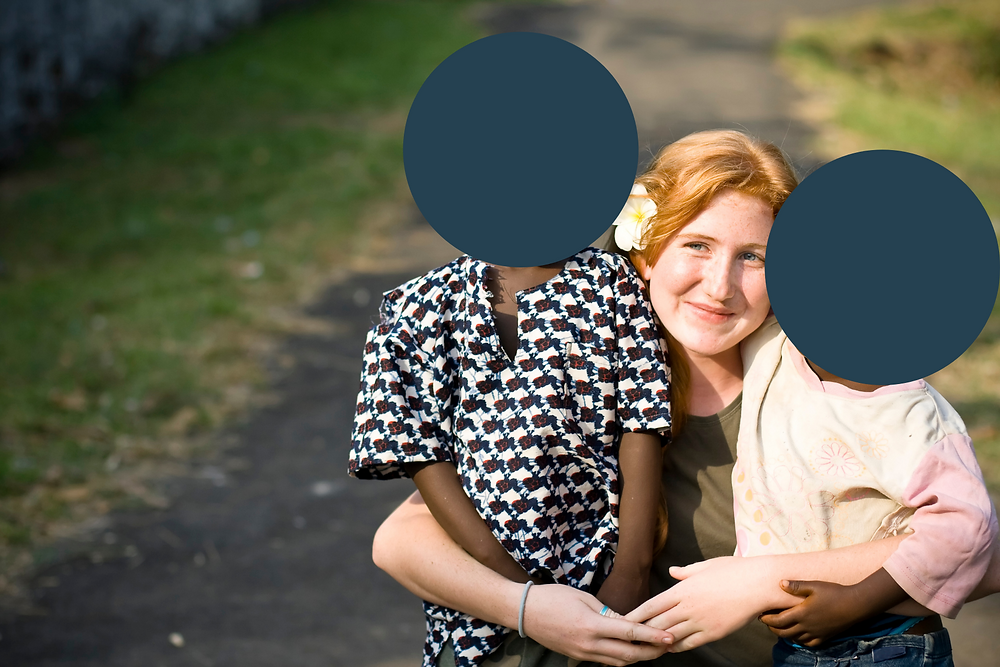 A picture of a white women with two Black children. The children's faces are covered for their privacy.