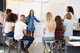 Schoolgirl presenting in front of scienc