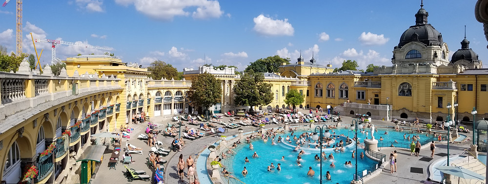 A panorama of the geothermal baths. Bright blue skies with pale yellow buildings of the palace like structure. Multiple pools and hundreds of people.
