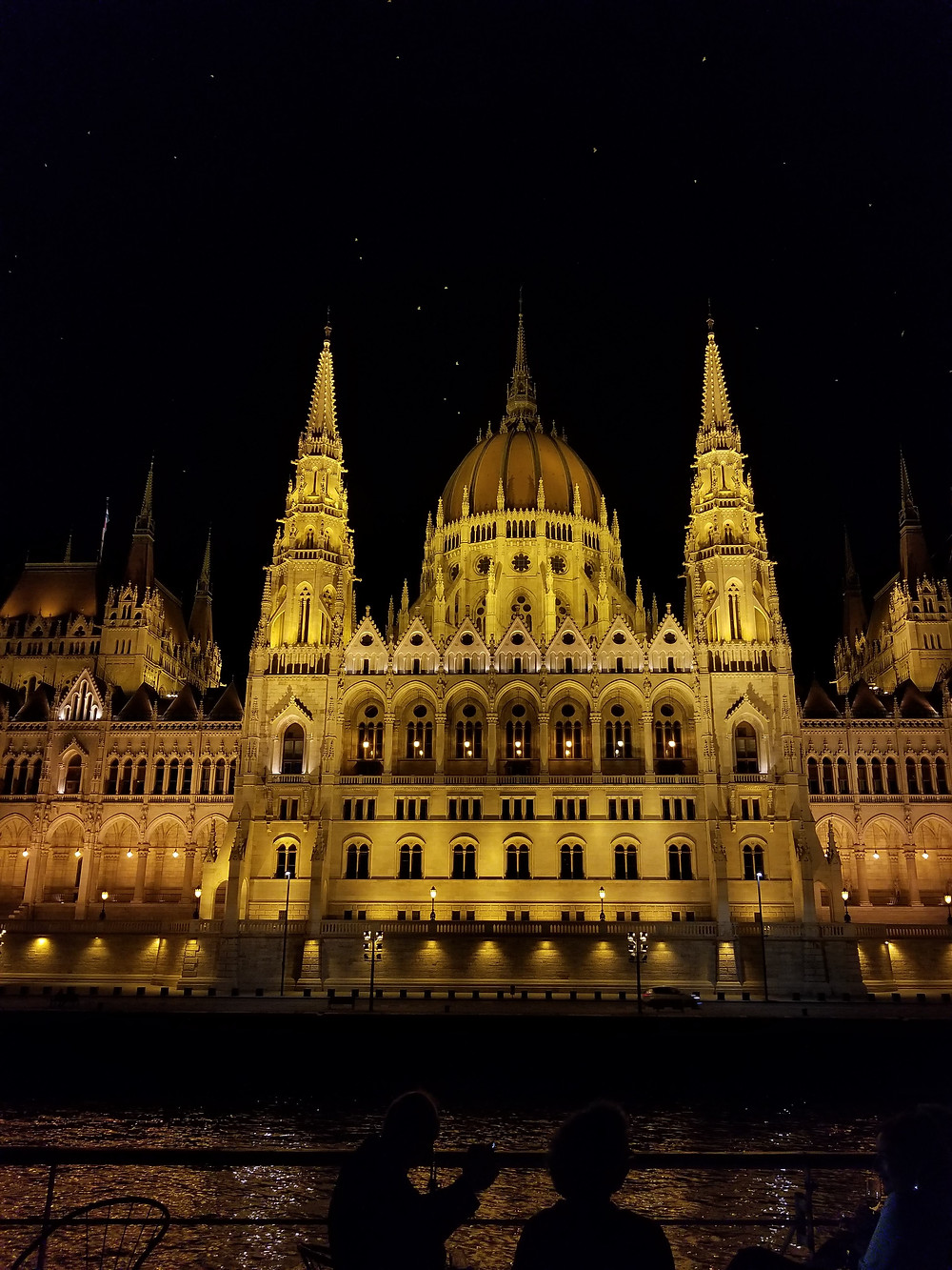 The Budapest Parliament building lit up at night from the Danube River.