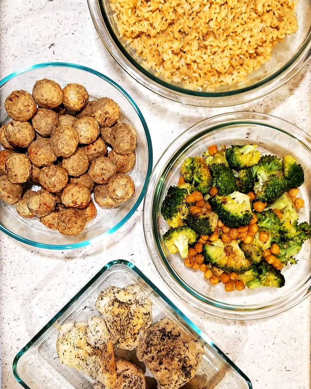 Image of meal prep containers containing rice, meatballs, mixed vegetables, and chicken.