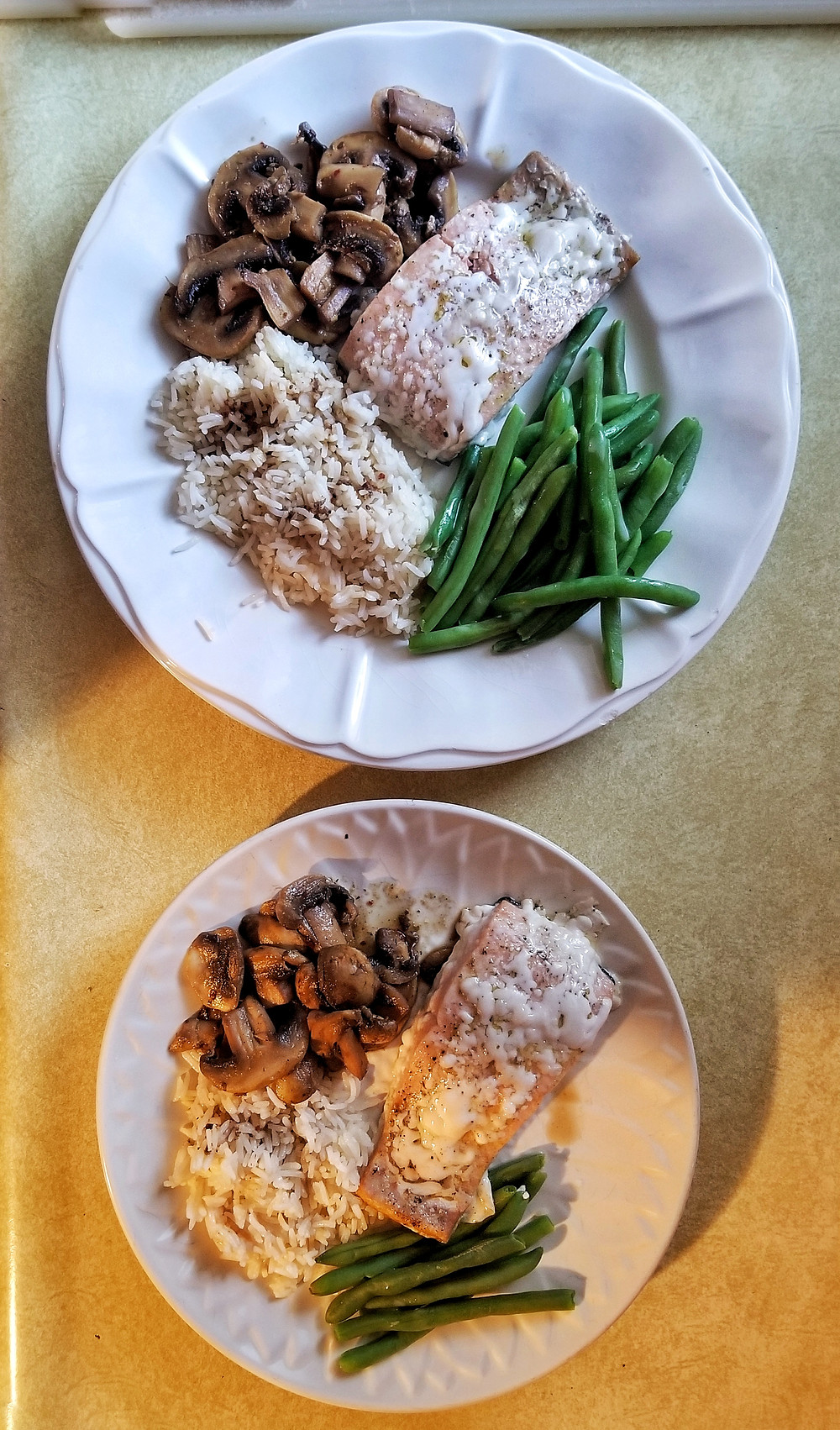 Two plates featuring salmon, mushrooms, green beans, and rice.