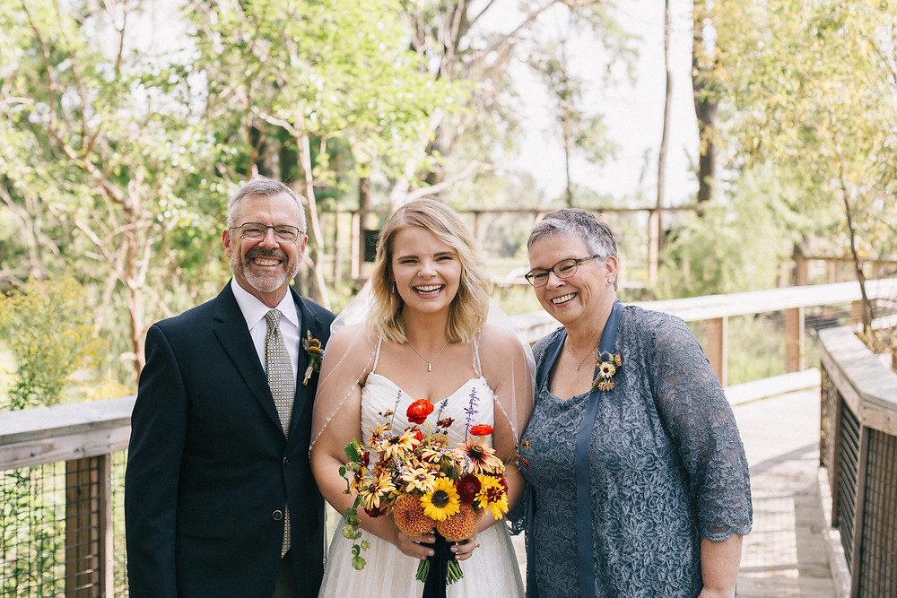 Kayla with her mom and dad on her wedding day, holding a bouquet of flowers.