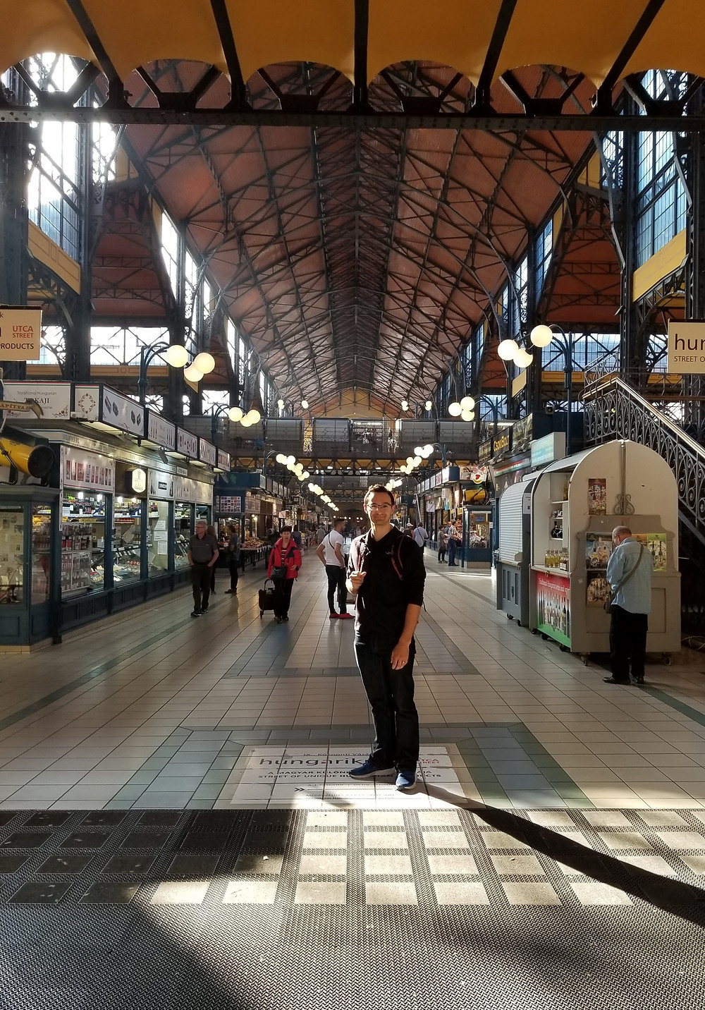 Anthony at the entrance of the Grand Market, shop stalls on both sides with sunlight streaming through the roof