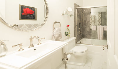 Gorgeous all-white bathroom featuring brushed metal hardware and a dark grey backsplash in the shower.