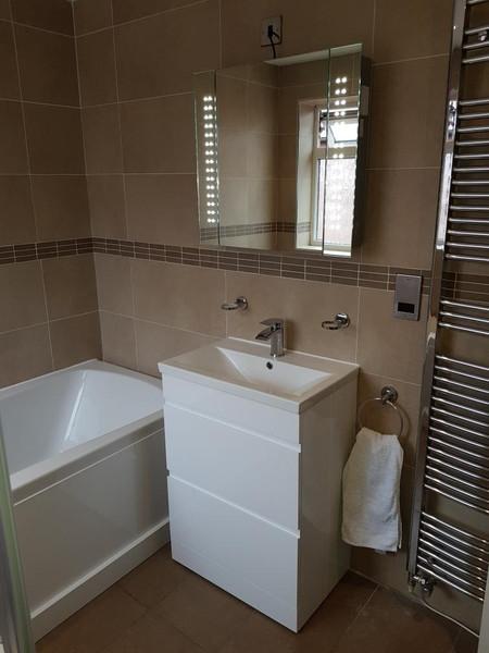 warm bathroom with tall chrome radiator