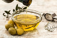 olive oil being poured into a bowl with olives next to it
