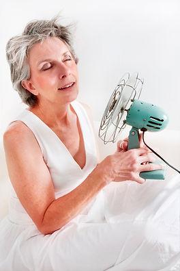 A woman having a hot flash using a fan t