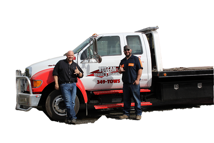 two men standing in front of a red and white vulcan towing vehicle