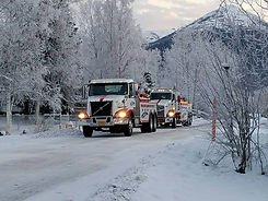 two white and red vulcan towing trucks in a winter scene