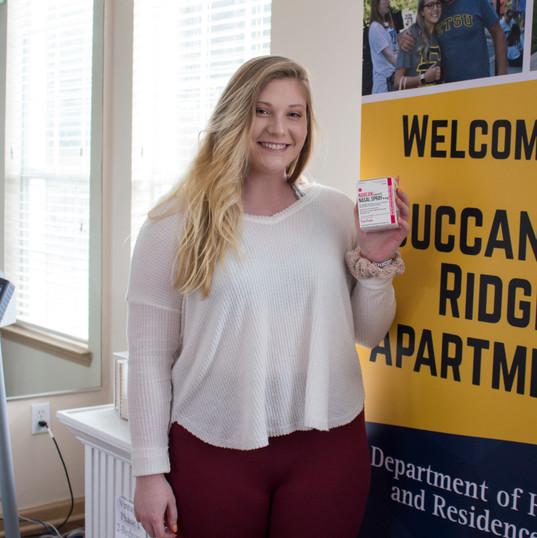 Residential Housing Advisor, Michaela Brewer, holding Narcan Nasal Spray