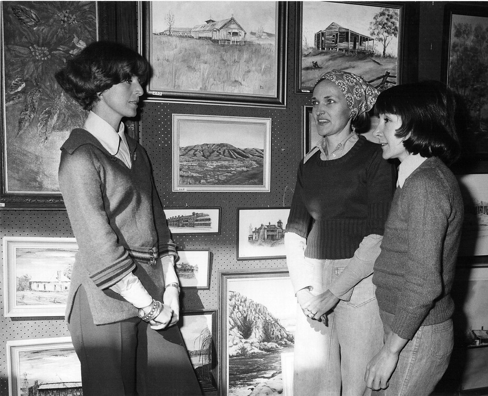 Army Art volunteer committee members at exhibition enjoying displayed artwork