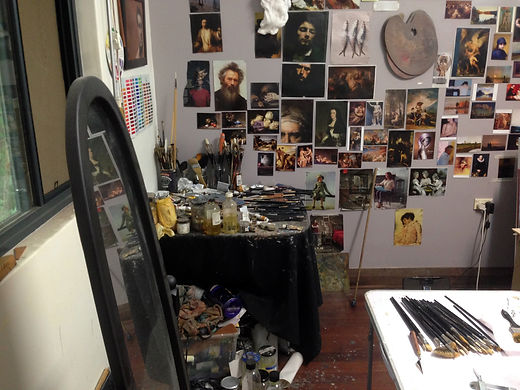 Painter Peter Barker's art studio with referece images and art tools