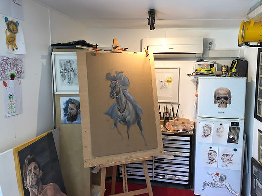Artist Ben Pronk's art studio with works in progress, portraits and skull painted on fridge