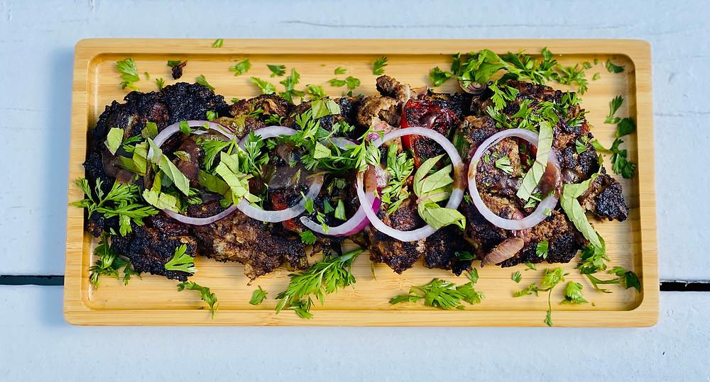Chapli kabab garnished with cilantro and sliced onions
