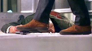 McQueen walking on water the bad guy's large frame automatic pistol and shat-tered safety glass in the climactic scene of Bullitt. Note the snuff brown chukkas.