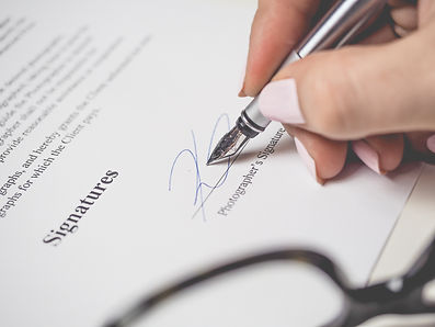 person-holding-silver-pen-signing-photog