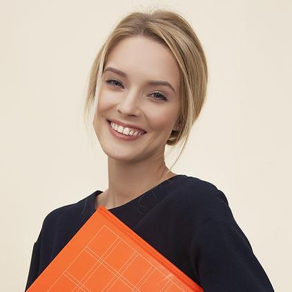 smiling%20woman%20standing%20while%20holding%20orange%20folder_edited.jpg