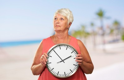 Woman holding clock retirement time running out